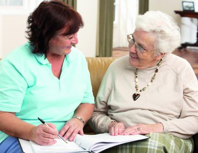 Senior Woman In Discussion With Health Visitor At Home Writing Down Information Smiling At Each Other