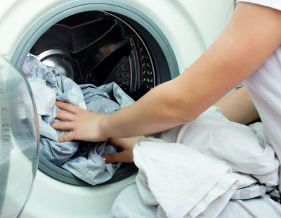 hands of a young girl put clothes in the washing machine drum